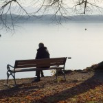 person alone on bench by lake-crop